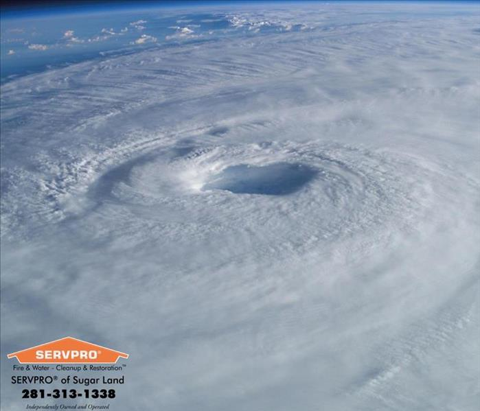 Top view of hurricane with the eye wall near the center.  SERVPRO of Sugar Land logo & information in the bottom left corner