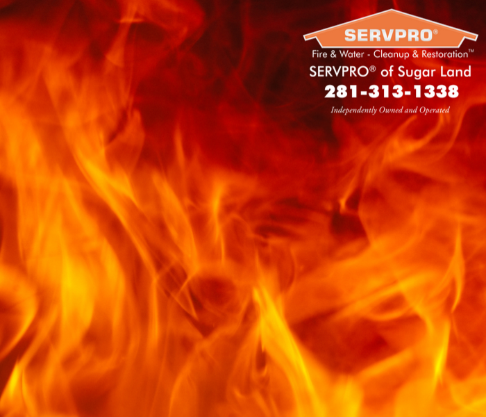 Flames cover the entire photo.  SERVPRO of Sugar Land logo and company information on the far top right hand corner.