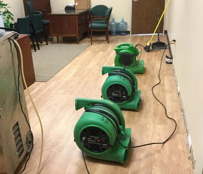 Three green drying equipment in office on wood floors and near the walls.  Wooden desk in the back of the room.