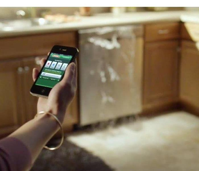 SERVPRO app on phone in front of overflowing dish washer